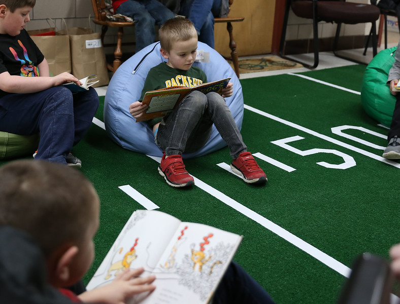 HOLLY PELCZYNSKI - BENNINGTON BANNER First grader Bailey Hunter reads a book quietly during the silent reading Super Bowl event held at Bennington Elementary School to celebrate the upcoming Super Bowl game and promote reading.