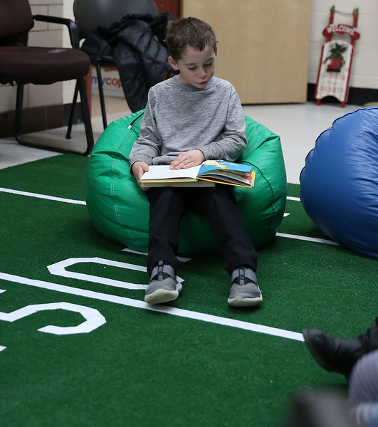 HOLLY PELCZYNSKI - BENNINGTON BANNER First grader Emmett Susee reads a book on the astroturf during the reading Super Bowl event held in the lobby of Bennington Elementary School. The event, held to promote reading and celebrate the upcoming big game  featured 30 minute slots of silent reading, on astroturf and comfortable seating for each grade.
