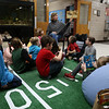 HOLLY PELCZYNSKI - BENNINGTON BANNER Bennington Elementary First grade teacher Leigh Jelley reads a picture book to her students during a reading Super Bowl program held to promote reading and celebrate the upcoming Super Bowl on Friday in Bennington.