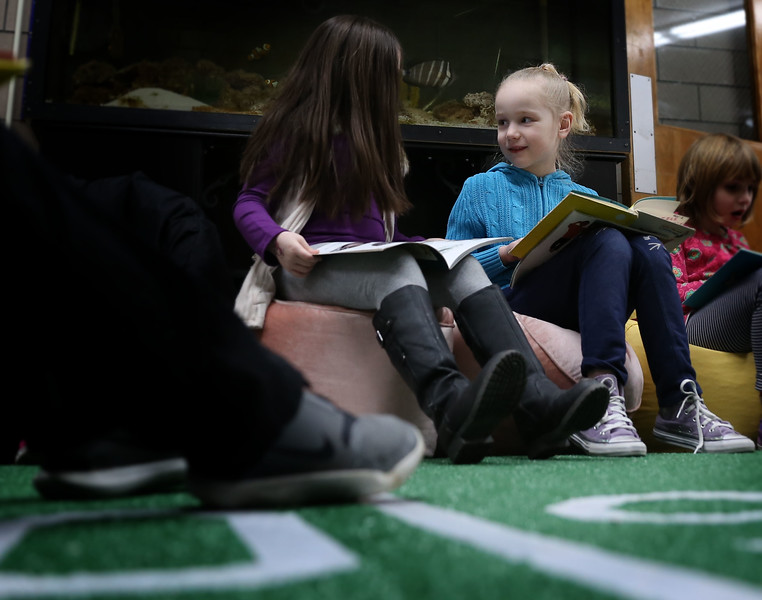 HOLLY PELCZYNSKI - BENNINGTON BANNER First graders Haiden Brandmeyer and Mireille Watson read books together on Friday afternoon during the reading Super Bowl event held in the lobby of Bennington Elementary School. The event, held to promote reading and celebrate the upcoming big game  featured 30 minute slots of silent reading, on astroturf and comfortable seating for each grade.