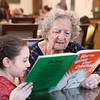 """HOLLY PELCZYNSKI - BENNINGTON BANNER Loretta Lemieux and Helena Bean 2nd grader at Grace Christian School  read """"How the grinch stole Christmas"""" together at the Bennington Project of Independence on Wednesday during a visit from the school to celebrate the birthday of Dr. Seuss."""