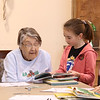 HOLLY PELCZYNSKI - BENNINGTON BANNER<br /> HOLLY PELCZYNSKI - BENNINGTON BANNER<br /> Frances Hunt enjoys a book with Grace Christian 2nd grader Emersyn Powers on Wednesday morning at the Bennington Project Independence during a visit from the students of Grace Christian School in celebration of the birthday of Dr. Seuss.