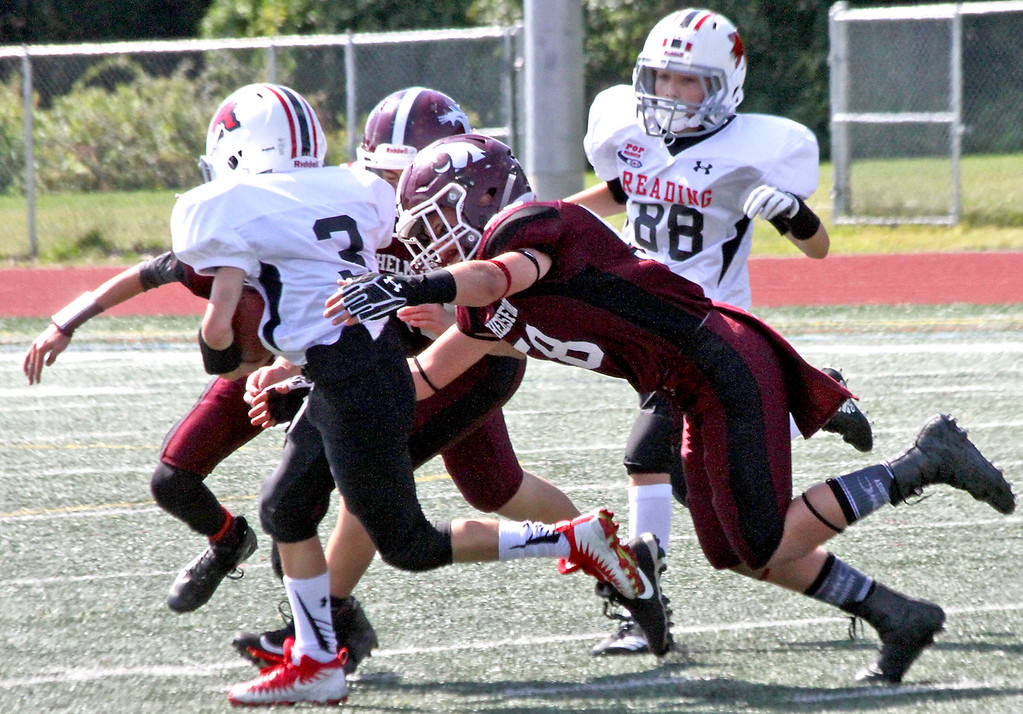 """. Chelmsford \""""C\"""" team member about to take down \""""C\"""" team Reading ballcarrier #3-Jack Dougherty, at the McCarthy MS Field. SUN Photo by David H. Brow"""
