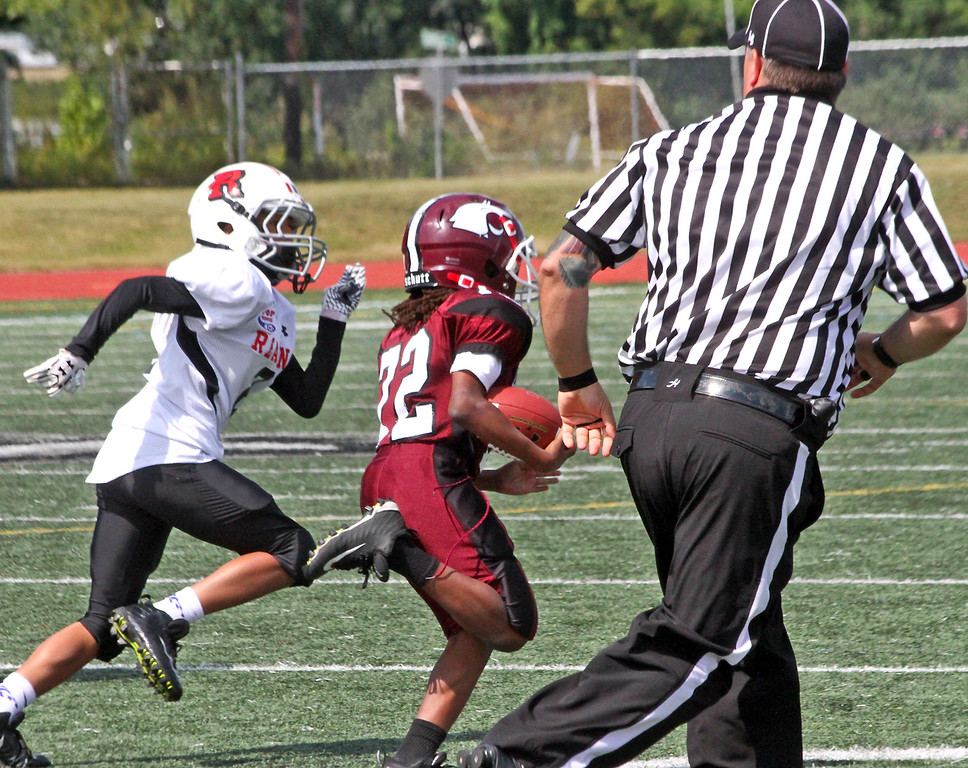 """. Chelmsford\'s \""""C\"""" team player # 72-Isaiah Adams, breaks away from Reading players and runs onto a TD to give Chelmsford a winning score. SUN Photo by David H. Brow"""