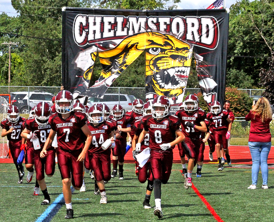 """. Chelmsford Pop Warner \""""B\"""" team burst onto the field at McCarthy MS for their game with Reading. SUN Photo by David H. Brow"""