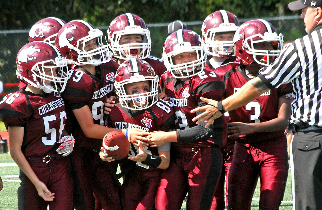 """. Chelmsford Pop Warner \""""C\"""" team members surround player #88-Ty Cannistraro, after he recovered a fumble from a Reading player. SUN Photo by David H. Brow"""