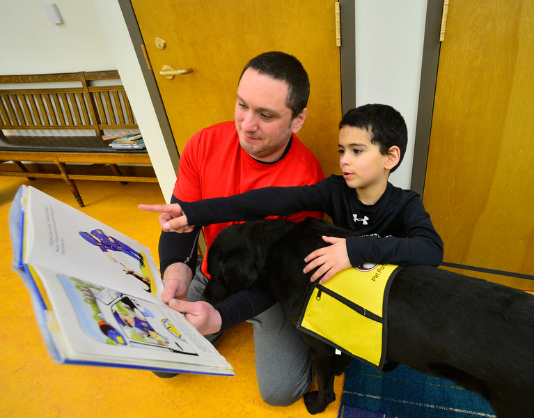 """KRISTOPHER RADDER — BRATTLEBORO REFORMER<br /> David Hoyer helps David John Hoyer, 7, as they read """"Gloria"""" to Kelso, a labrador retriever, during a Pages & Paws, read to a dog program at the Brooks Memorial Library on Wednesday, Feb. 26, 2020."""