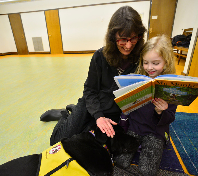 """KRISTOPHER RADDER — BRATTLEBORO REFORMER<br /> Kai Bossard-Kruger reads """"Mr. Monkey Takes a Hike"""" as Kelso, a labrador retriever, snuggles into her as mother Chandra watches during a Pages & Paws, read to a dog program at the Brooks Memorial Library on Wednesday, Feb. 26, 2020."""