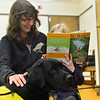 "KRISTOPHER RADDER — BRATTLEBORO REFORMER<br /> Kai Bossard-Kruger reads ""Mr. Monkey Takes a Hike"" as Kelso, a labrador retriever, snuggles into her as mother Chandra watches during a Pages & Paws, read to a dog program at the Brooks Memorial Library on Wednesday, Feb. 26, 2020."