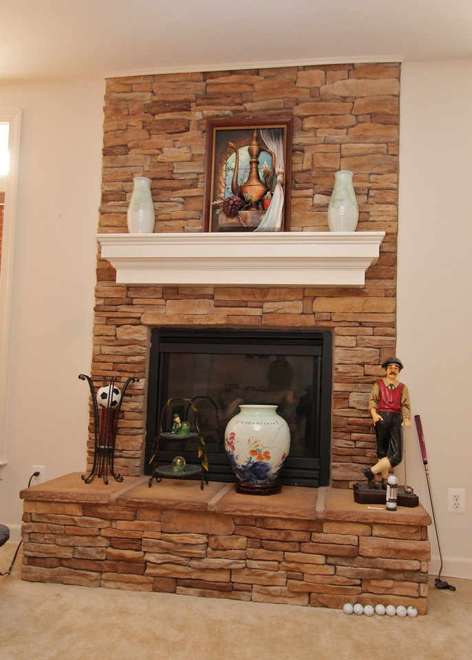 Gas fireplace in family room features natural stone and wood mantel
