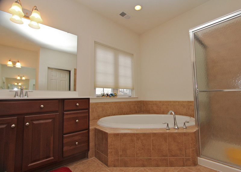 Master Bath feature two separate vanities along with ceramic tile, tub and shower.