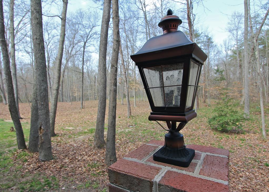 Handsome coach lanterns adorn brick columns in the back.