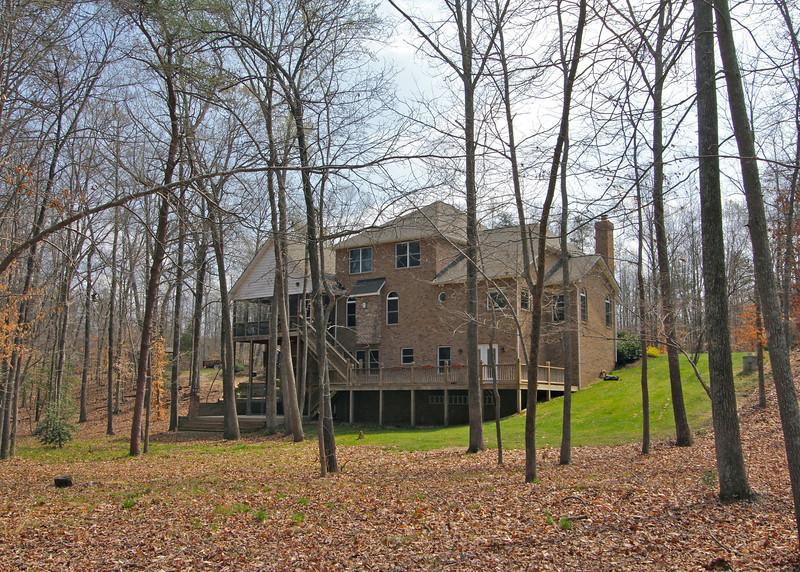 Back of home features large screened porch and massive tiered decks overlooking wooded acreage and stream.
