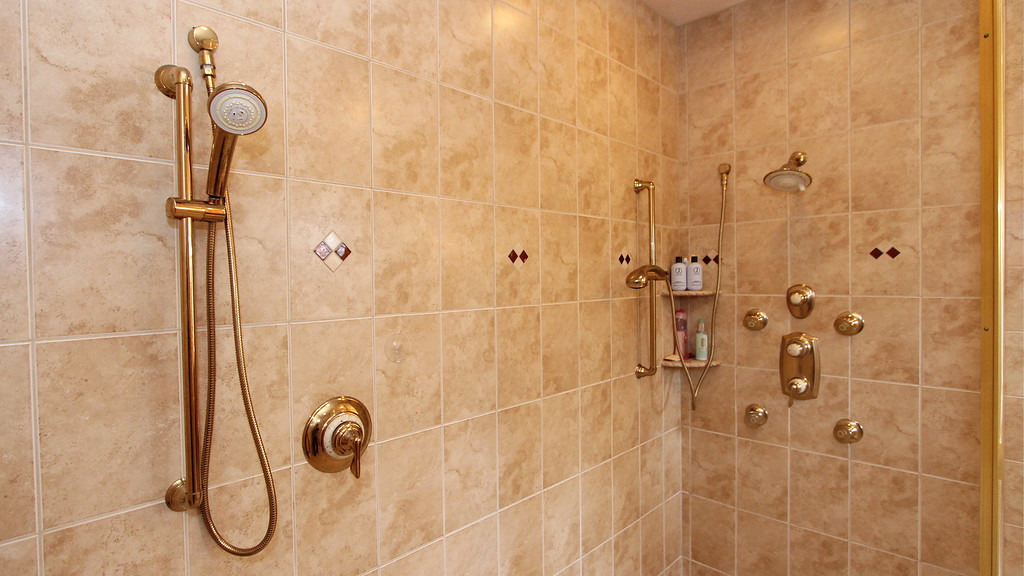 MBA walk-in glass and tile shower has three shower stations!