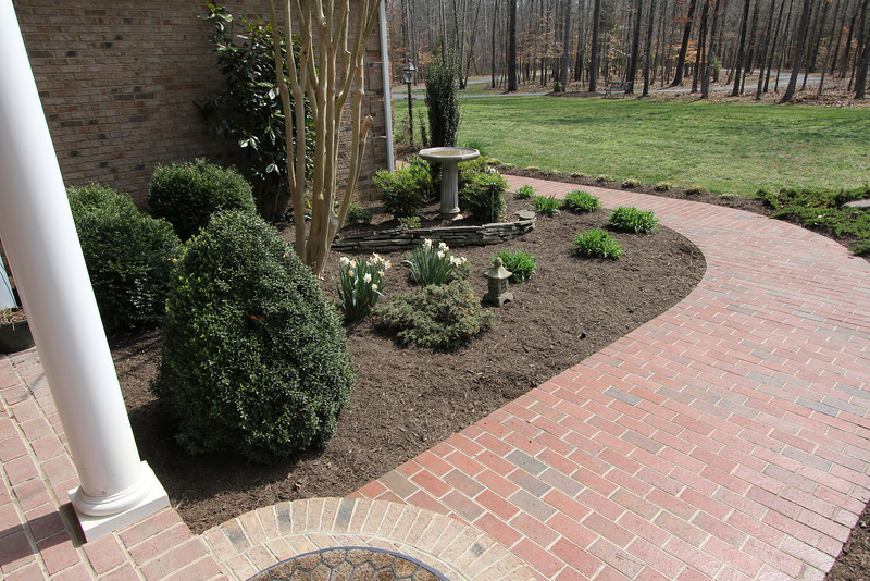 Lovely landscaping greets guests along the brick pathway to the front entrance.
