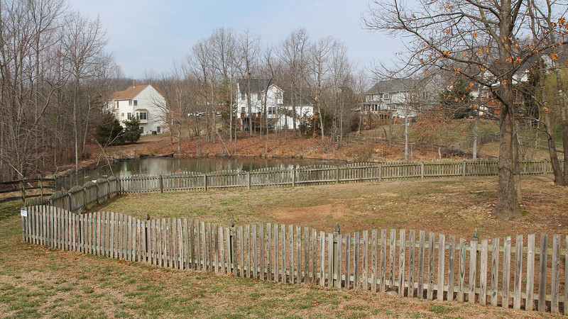 Huge fenced back yard overlooks a pond