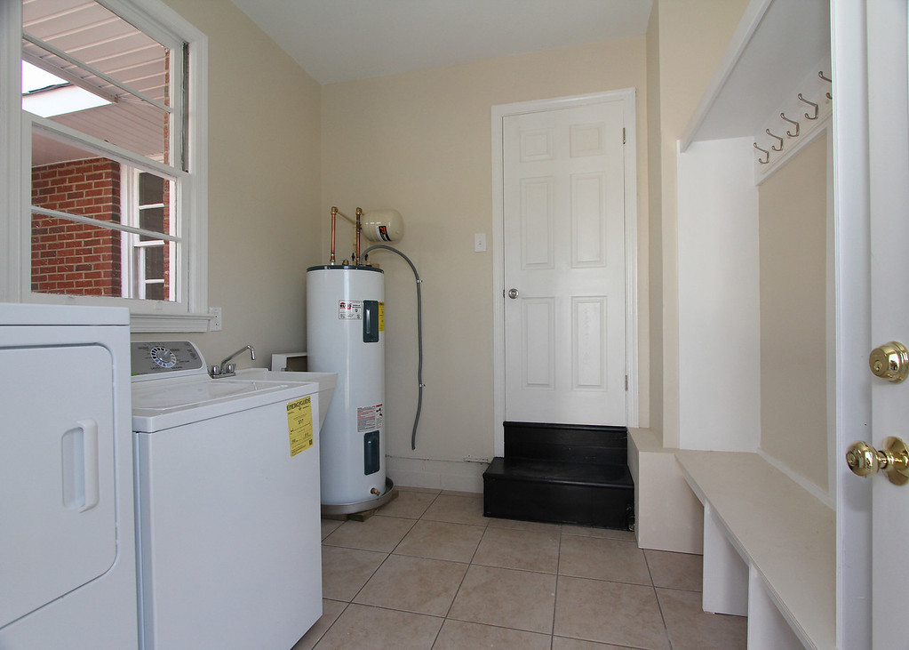 Rear entrance comes through a great mud/laundry room featuring new washer, dryer, hot water heater, utility sink and custom coat/shoe rack.