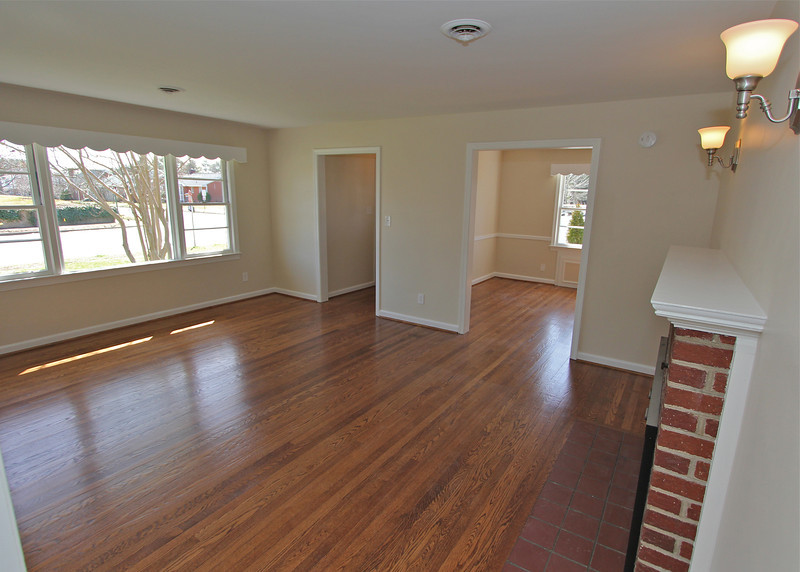Huge living room w/large picture window, brick fireplace and wonderfully refinished hardwood flooring.