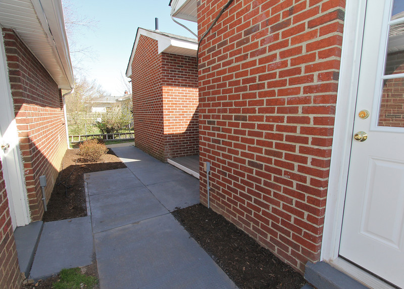 Rear of home showing side door access to the garage (on the left) as well as a private patio deck area (on the right).