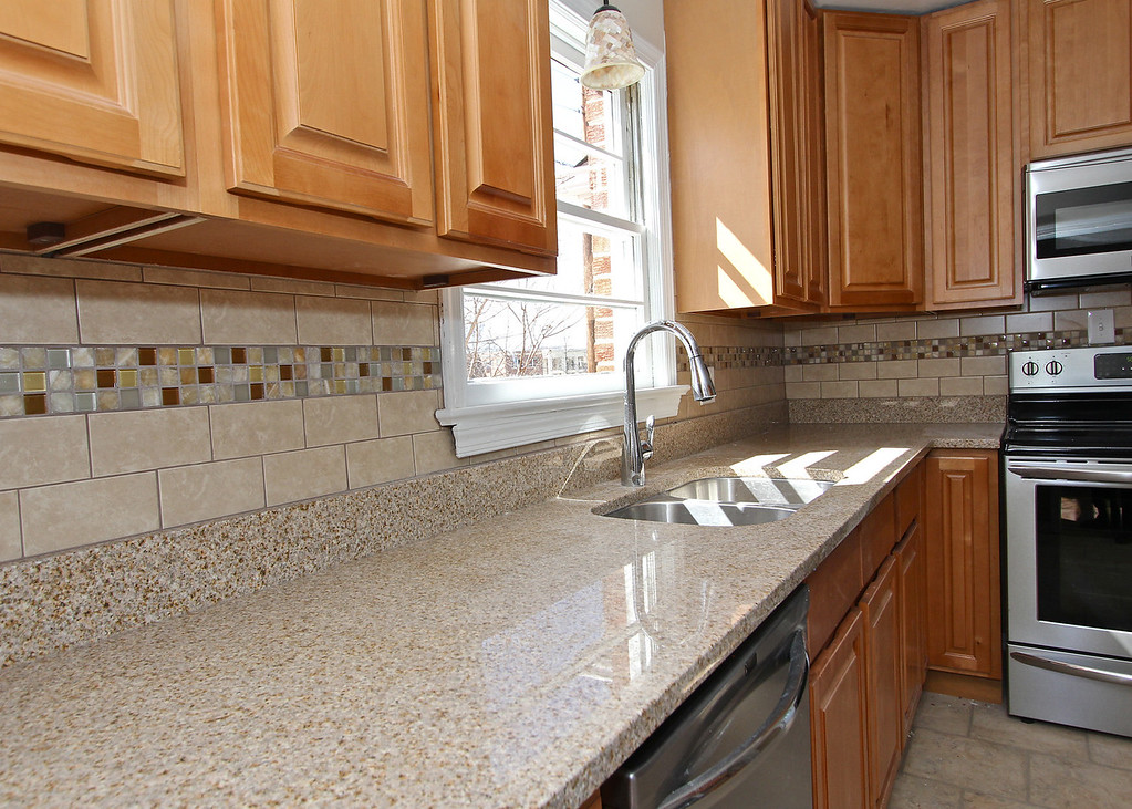Granite counters and custom ceramic tile work add to this kitchen's amazing makeover.