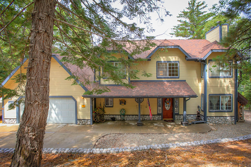 Tree-shaded front access with graveled parking area, double garage