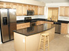 Kitchen with black granite , stainless steel, and raised panel maple cabinets