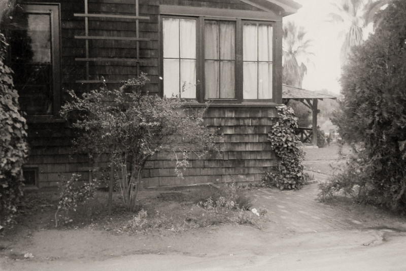 East side of the house looking at the present day sun-room.  Front porch has been enclosed. Bedroom window is to the left.