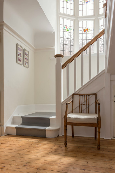 Original reconditioned floorboards with exposed tread on stairs.