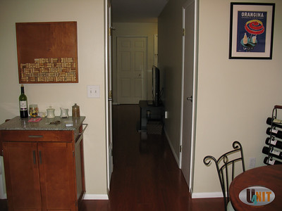 Dining area leads to hall way with storage closet on left and half bathroom on right.