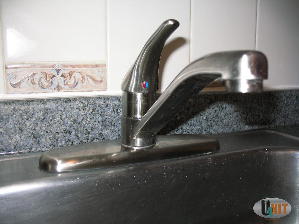 Brushed nickel kitchen faucet detail.