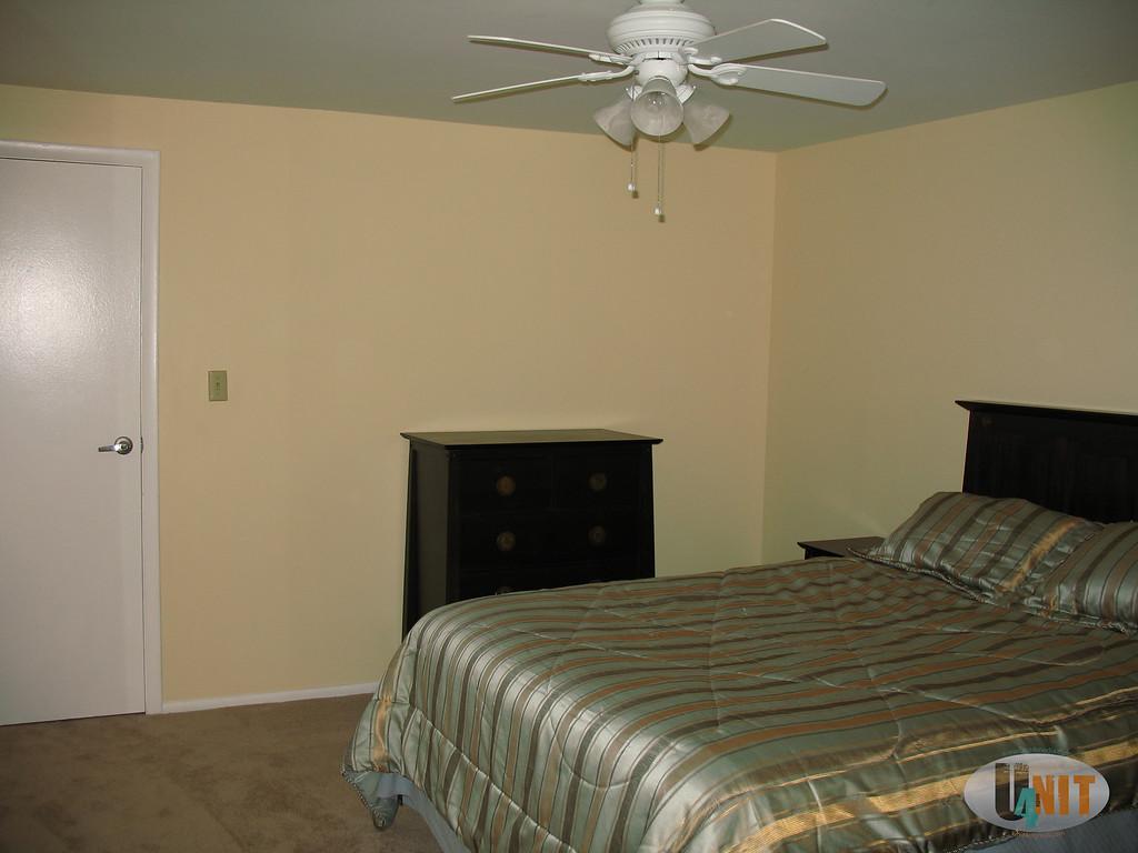 Airy carpeted bedroom with floor to ceiling window overlooking front door, big lit closet.