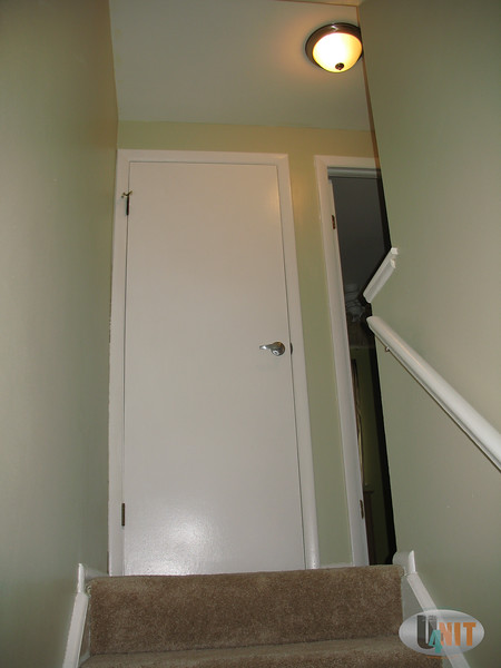 Carpeted stairwell that leads to a linen closet. All upstairs doors have brushed nickel door handles.