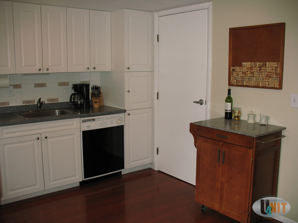 Utility closet in kitchen housing service panel and hot water heater also storage area.