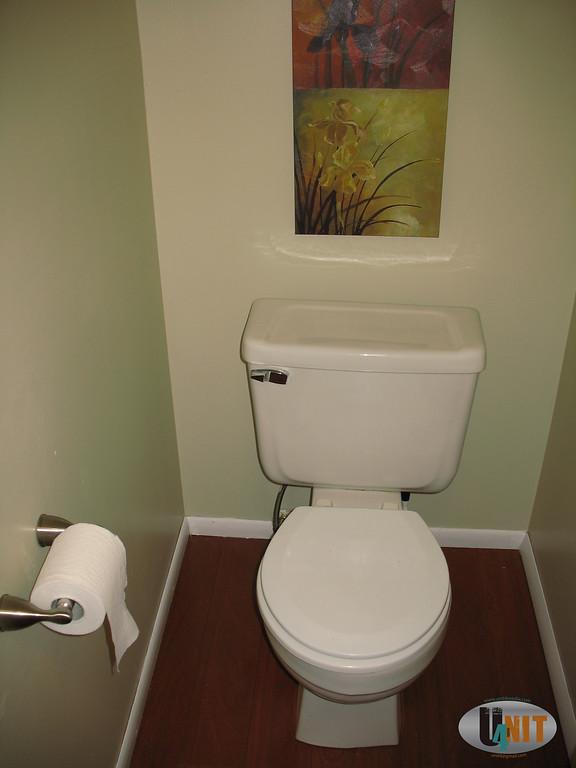 Half bathroom mahogany flooring, large mirror and corner basin.