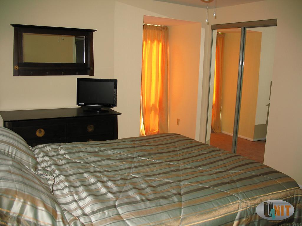 Airy carpeted bedroom with floor to ceiling window overlooking front door, big lit closet with full length mirror sliding doors.