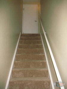 Carpeted stairwell that leads to a linen closet.