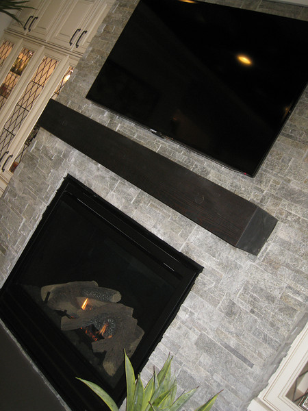 Fireplace with stone surround and wood mantle