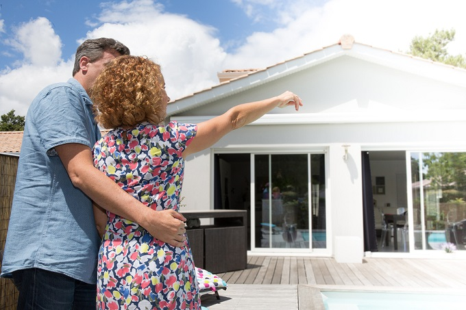 Couple Embracing In Front Of New Modern House, Back View