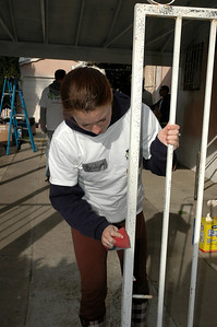 Sanding the wrought iron to prepare for painting.