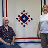 Margaret Moss (seated) and her daughter, Elizabeth Allen, in front of a family quilt from the 1940's. (Billy Hefton / Enid News & Eagle)
