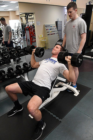 2nd Lt. Hunter Richardson spots for 2nd Lt. Grant Hamilton as they work out at the fitness center at Vance Air Force Base Friday January 20, 2017. (Billy Hefton / Enid News & Eagle)