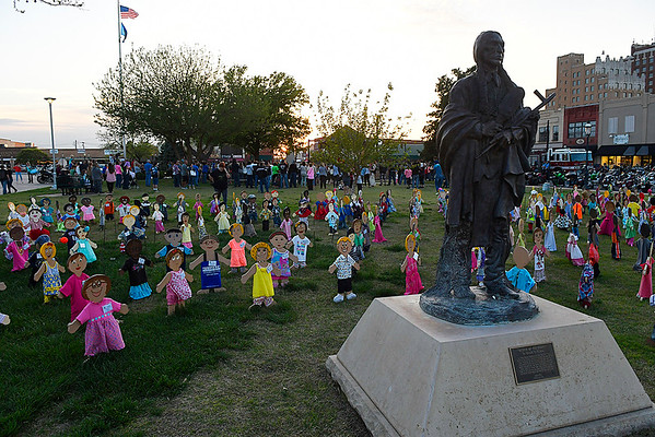 """The Harold Holden sclupture """"Keeper of the Plains"""" stands over wooden kids represenring abused children during a memorial service for Enid's Baby Boy Angel Friday April 14, 2017 at the Garfield County Courthouse gazebo. (Billy Hefton / Enid News & Eagle)"""