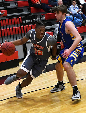 NOC Enid's Sebastian Gray dribbles the baseline against Eastern's Todd Dawkins Thursday February 16, 2017 at the NOC Mabee Center. (Billy Hefton / Enid News & Eagle)