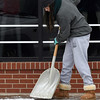 Mazzy Priest cleans snow from a sidewalk on north Grand Ave. Friday January 6, 2017. (Billy Hefton / Enid News & Eagle)