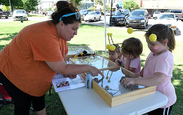 Ashley Knoch, a Ph.D. student from Oklahoma State University, points out different types of bees to kids during the Bee Invasion Saturday May 13, 2017 on the Garfield County Courthouse lawn. (Billy Hefton / Enid News & Eagle)