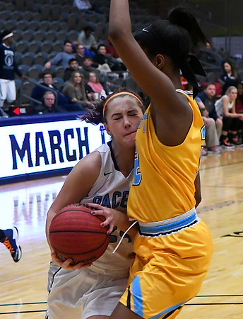 Enid's Izzy Plunkett runs into Putnam City West's Ce'Nara Skanes as she drives to the basket Tuesday February 14, 2017 at the Central National Bank Center. (Billy Hefton / Enid News & Eagle)