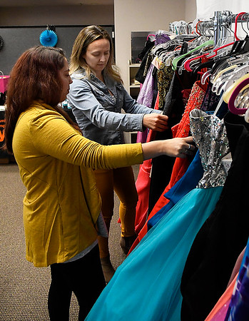 Sara Hamdani, YWCA Enid counselor and Amanda Priest, YWCA Enid youth coordinator, look through dresses Friday March 10, 2017 that have donated to the YWCA's Project Cinderella. (Billy Hefton / Enid News & Eagle)