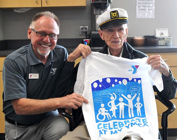 Denny Price Family YMCA executive director Ken Rapp, left, gives Glenn Semke, right, a T-shirt for Semke's 100th birthday on Monday. (James Neal / Enid News & Eagle)