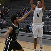 Enid's Tyler Johnson shoots over Rubell Goe of Bishop McGuinness Saturday February 11, 2017 at the Central National Bank Center. (Billy Hefton / Enid News & Eagle)