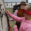 Sarah Hardaway smiles as Samantha Creveling plays Pin the Tail on the Horse during the Chisholm Trail 150 Festival Saturday April 1, 2017 at the Cherokee Strip Regional Heritage Center. (Billy Hefton / Enid News & Eagle)
